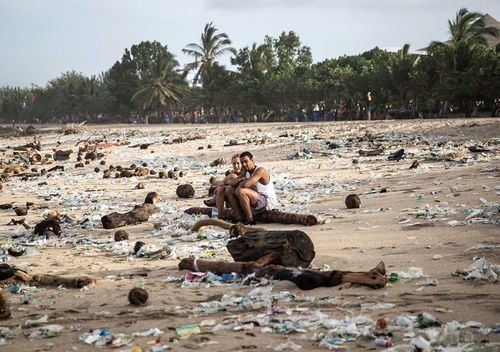 Tourists sit among plastic trash on Kuta Beach, Indonesia. The sight of trash washed up on Kuta beach has become an annual phenomenon as piles of debris are carried to the beach by strong currents during the winter months. (Getty Images)