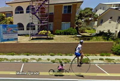 A stuffed penguin takes a ride behind the penny-farthing bike. (Google Street View)