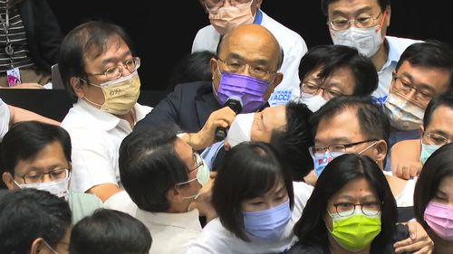 Premier Su Tseng-chang, in purple mask, tries to make a policy speech amid a scuffle between opposition Nationalist party and ruling Democratic Progressive Party lawmakers during a parliament session in Taipei.