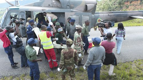 Soldiers and paramedics carry injured survivors from a helicopter in Chimanimani about 600 kilometres south east of Harare, Zimbabwe, Tuesday March, 19, 2019.