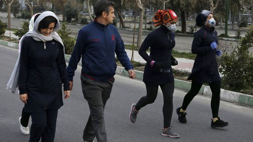 Two women jog with face masks on as others walk while enjoying their weekend afternoon at Pardisan Park in Tehran, Iran, Friday, Feb. 28, 2020