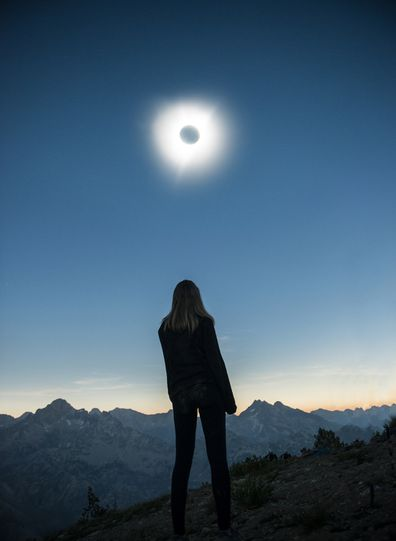 A woman watching an eclipse in the USA, Idaho at Sawtooth Range.