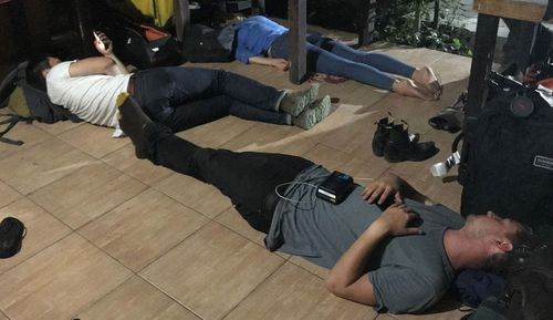 Covering a crisis: Reporter Sophie Walsh and her team attempt to grab an hour or two of sleep on the floor between television crosses. Lost bags and equipment have also contributed to difficulties sending satellite links back to Australia.