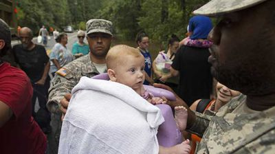 Members of the Louisiana Army National Guard load 3-month-old baby Ember Blount onto a truck as they rescue people from rising floodwater. (AP)