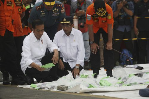 Indonesian President, Joko Widodo looks at some of the recovered items of victims.