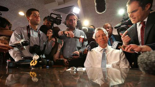 John Kasich (seated) is surrounded by the press at a diner in Philadelphia. (AAP)