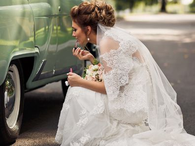 Bride putting on makeup in car reflection