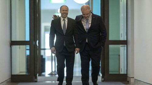 Prime Minister Scott Morrison right, walks with Deputy Leader of the Liberal Party Josh Frydenberg.