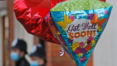 Balloons are fixed to a railing as Police officers stand outside King Edward VII's hospital in London. (AP Photo/Frank Augstein)