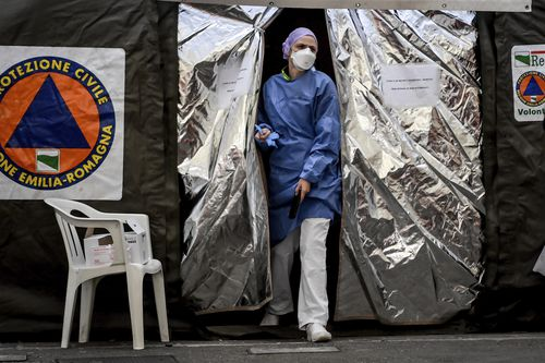A paramedics wearing a mask gets out of a tent set up by the Italian Civil Protection outside the emergency ward of the Piacenza hospital, northern Italy, Thursday, Feb. 27, 2020. Picture: Claudia Firlan