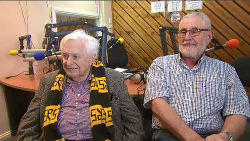 Tommy Carter sits draped in Richmond colours in the Casey radio station studio.