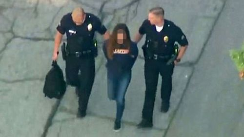 A 12-year-old girl, suspected of the US school shooting, is led away by police. (AAP)