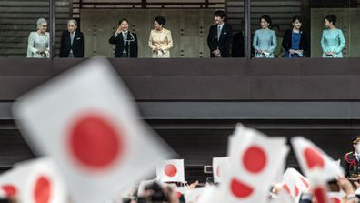 Well-wishers wave flags as Emperor Naruhito of Japan waves after delivering a traditional New Year's greeting at the Imperial Palace on January 2, 2020 in Tokyo, Japan.