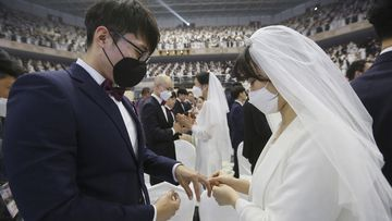 A couple wearing face masks exchanges their rings in a mass wedding ceremony at the Cheong Shim Peace World Center in Gapyeong, South Korea, Friday, Feb. 7, 2020. South Korean and foreign couples exchanged or reaffirmed marriage vows in the Unification Church's mass wedding arranged by Hak Ja Han Moon, wife of the late Rev. Sun Myung Moon, the controversial founder of the church.
