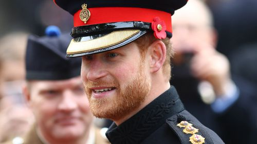 Britain's Prince Harry speaks to members of the armed forces and their and relatives during his visit to the Field of Remembrance at Westminster Abbey in central London, Britain. (AAP)