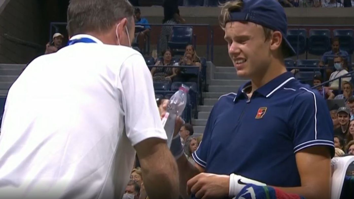 Holger Rune gets treatment on his leg during his match against Novak Djokovic.