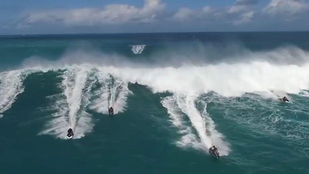 Jetskis forced to flee monster wave