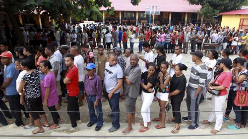 People queue up to give their vote during the presidential election at a polling station in Dili, East Timor.