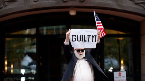 An activist reacts to the announcement that former Trump campaign chairman Paul Manafort has been found guilty to count one in US District Court in Alexandria, Virginia.