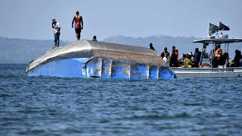Rescue workers observe the capsized MV Nyerere passenger ferry as it lies upturned near Ukara Island, Tanzania. Burials have started of the more than 200 people who died when the ferry capsized on Lake Victoria, while the country's Defence Minister said no further survivors were likely to be found and search efforts had ended. (AAP)