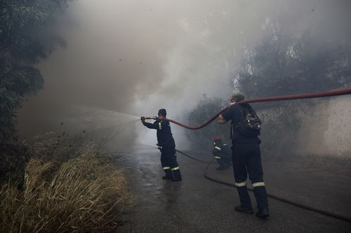Firefighters try to extinguish flames during a forest fire in Neo Voutsa, north-east of Athens. Picture: AAP
