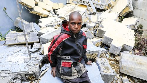 An undated handout photo made available on 23 March 2018 by UNICEF shows ten-year-old Abel Jeffery sitting amongst the rubble of a building in Mendi, Papua New Guinea. Papua New Guinea was hit by a powerful 7.5-magnitude earthquake on 26 February 2018.