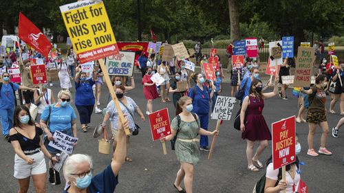 National Health Service (NHS) workers march from St. James' Park to Downing Street, London, Saturday Aug. 8, 2020, as part of a national protest over pay