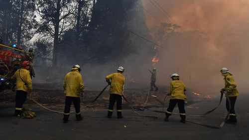 RFS protect a property impacted by bushfire on Hassall Road in Buxton due to the Green Wattle Creek Fire.