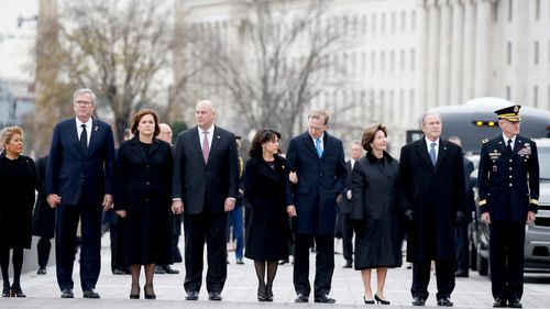 From right to left: former President George W. Bush, former first lady Laura Bush, Neil Bush, Sharon Bush, Bobby Koch, Doro Koch, Jeb Bush and Columba Bush, watch as former President George H.W. Bush is carried by a joint services military honour guard from the Capitol.