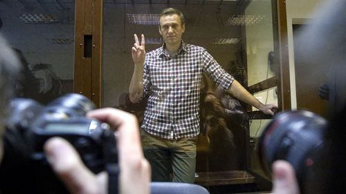 Opposition leader Alexei Navalny stands in a cage in the Babuskinsky District Court in Moscow, Russia, Saturday, Feb. 20, 2021.