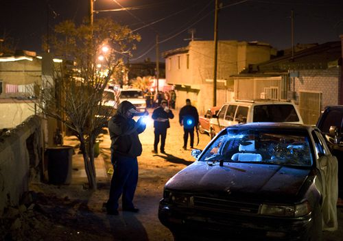 Police investigate the scene where a drug-related homicide occured in the city of Juarez.