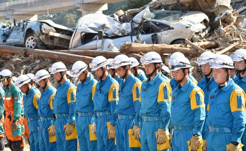 Emergency workers clearing up after the recent floods at Hiroshima mark a minute's silence during the anniversary of the atomic bombing. (Photo: AP).