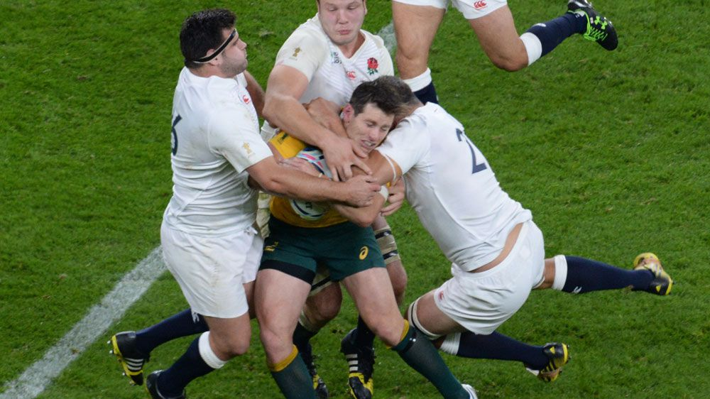 Bernard Foley is tackled by England players the last time the two teams met. (AFP)
