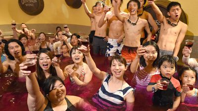 Japanese bathhouse guests celebrate the release of  France's Beaujolais Nouveau 2014 wine in a 'wine bath' party that is held over 10 days. (AAP)