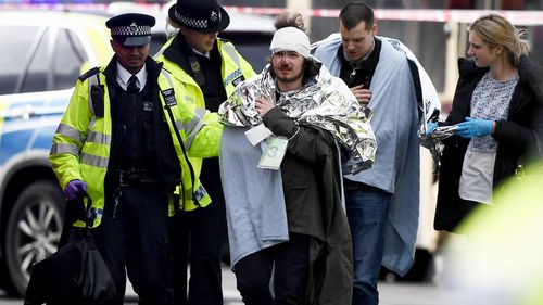 An injured man is taken away by police after the Westminster Bridge incident. (Getty)