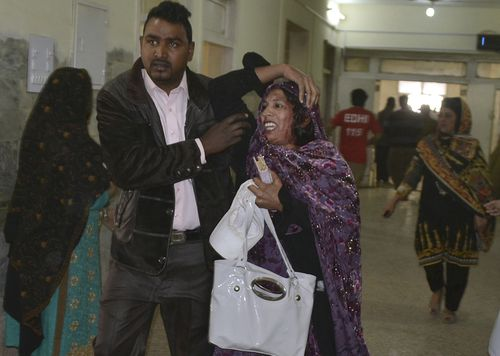 A man helps a woman injured in the suicide attack on a church, at a hospital in Quetta, Pakistan. (AAP)
