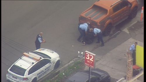 Police can be seen arresting a man on the street.