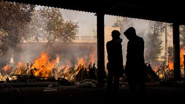 People are silhouetted against multiple burning funeral pyres of patients who died of COVID-19 in New Delhi, India.