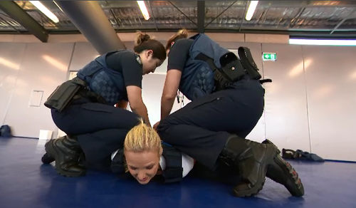Reporter Alexis Daish is pinned down by two recruits in a three point hold arrest. (Supplied)