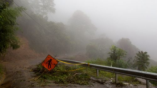 A men at work sign stands on a washed out road in Alajuelita on the outskirts of San Jose, Costa Rica. (AP)