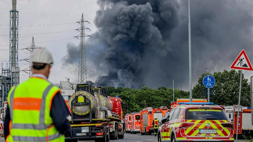 Emergency vehicles of the fire brigade, rescue services and police stand not far from an access road to the Chempark over which a dark cloud of smoke is rising in Leverkusen, Germany, Tuesday, July 27, 2021