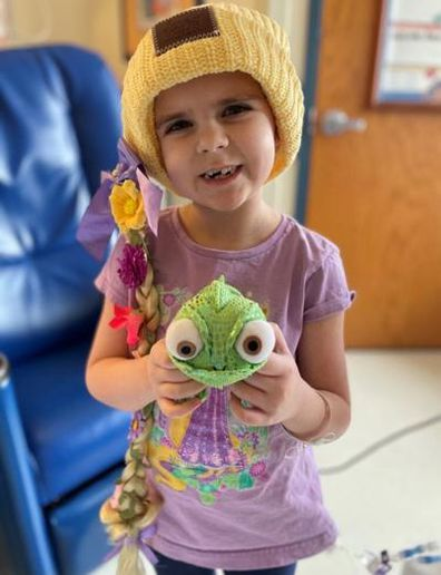 Young girl in hospital holding a toy frog.