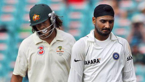 Harbhajan Singh, right, and Australia's Andrew Symonds walk past each other
