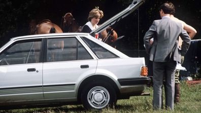 Princess Diana standing next to car given to her by Prince Charles