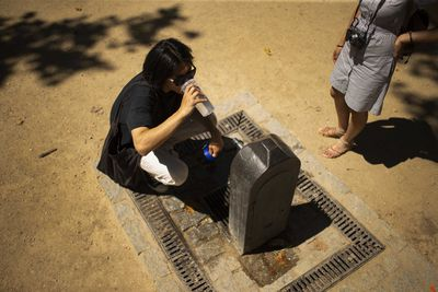 People drink water from a public fountain in Madrid. Much of Spain is on alert as the country's weather agency warns that temperatures could surpass 40 degrees Celsius (104 Fahrenheit) due to a hot air mass moving northward from the African continent.