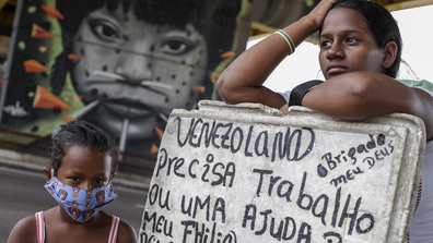 Melida Marquez, a 23-year-old Venezuelan woman holds a sign asking for job and help with her daughter Genesis, 6, at downtown Manaus on May 23 2020 in Manaus, Brazil. Melida arrived in Manaus a year ago, is pregnant with her fourth child and has no protective masks.