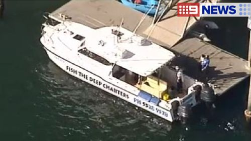 A charter boat near an ambulance at the The Spit. (9NEWS)