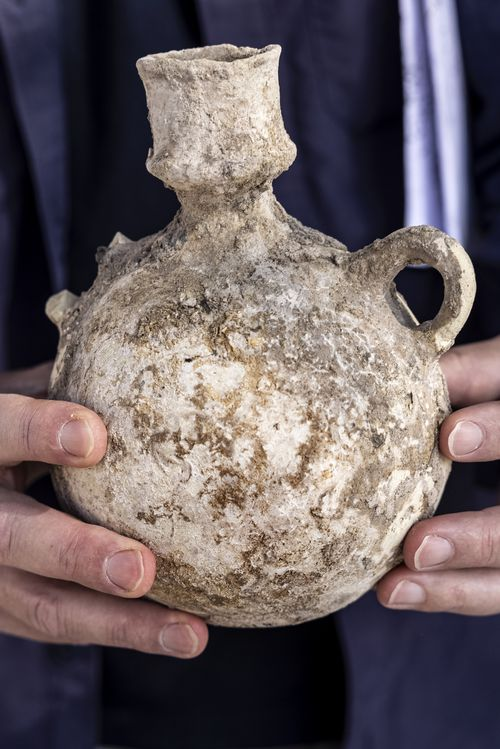 An Israel Antiquities Authority employe holds a jar unearthed from the winemaking complex.