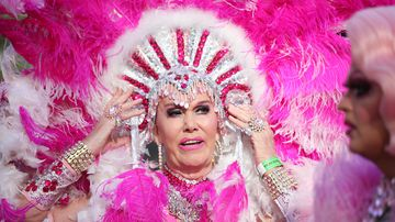 A drag queen adjusts her brilliant pink headdress. (AAP)