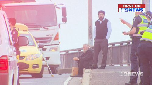 Rob, pictured seated, held the man's nearly severed arm in place while waiting for paramedics to arrive. (9NEWS)